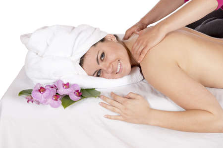 Spa therapy getting a back and shoulders massage by technician masseuse for happy pretty young brunette woman, wrapped in towel while enjoying aroma therapy laying on massage table  In studio on white background