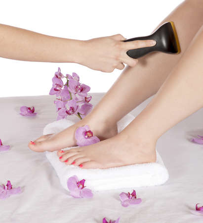 hair treatment: Spa therapy business is using laser to remove unwanted hair from the leg of a client while resting manicured feet on a towel, surrounded with purple orchids  Very floral and also have the benefits of aroma therapy  Stock Photo
