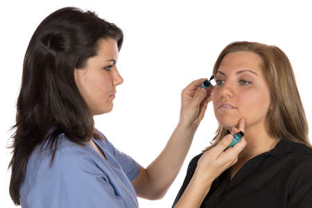 Two women one a very technical and professional beauty technician in scrubs work cloths applying make up on a blond woman Stock Photo