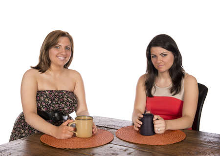 Two happy women sitting at a table each with a cup of coffee, or coco, casual formal dressed, in studio on white background  Stok Fotoğraf