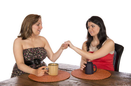 Woman shows her new engagement ring to another woman