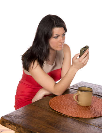 Pretty woman wearing dress ready for work is sitting at dining room table using cell phone and drinking coffee