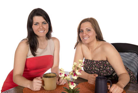 Two happy women sitting at a table each with a cup of coffee