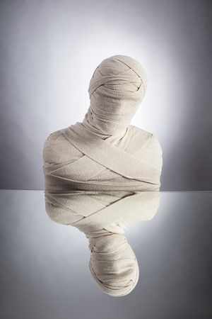 Awakening of Mummy, escape of everyday routine concept. Man wrapped in bandages as egyptian mummy.