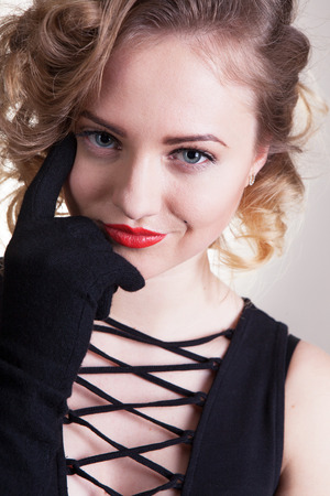 Pretty blond girl model like Marilyn Monroe, Madonna in black dress with red lips on white background. 50's Vintage Fashion and Style. Portrait of rich young woman, material girl, femme fatale 版權商用圖片