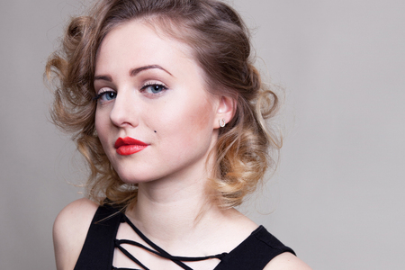 Pretty blond girl model like Marilyn Monroe, Madonna in black dress with red lips on white background. 50's Vintage Fashion and Style. Portrait of rich young woman, material girl, femme fatale 写真素材