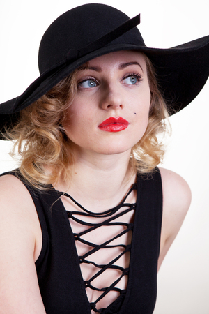 Pretty blond girl model like Marilyn Monroe, Madonna in black dress with red lips on white background.