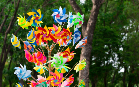 Many fun colorful pinwheels spinning in the wind at a carnival park. Stock Photo