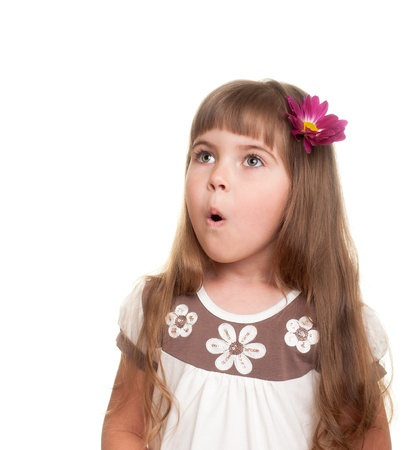 little girl surprised: cute little girl very surprised and looking up somewhere with bud of chrysanthemum in hair against white background Stock Photo