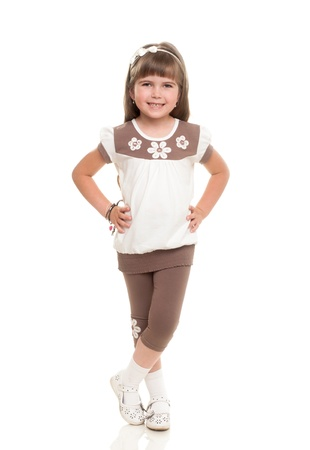 girl pose: cute little girl standing and smiling against white background
