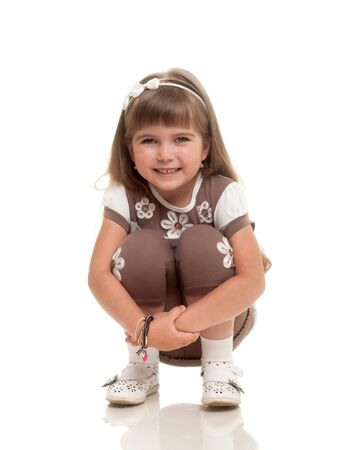 curtsy: cute little girl droped a curtsy and smiling against white background Stock Photo