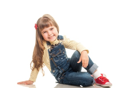 curtsy: cute little girl wearing jeans overall sitting on the floor and smiling on white background Stock Photo