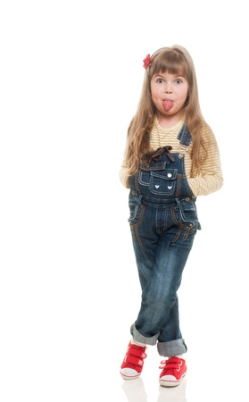 girl tongue: cute little girl wearing jeans overall posing in studio and sticking out her tongue on white