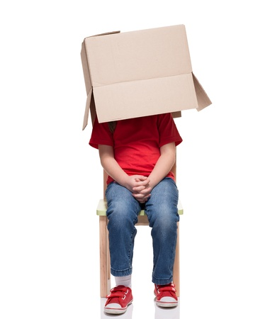 child sitting on a chair with big box covered head isolated on white photo