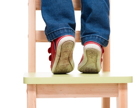 tiptoes: childs feet standing on the little chair on tiptoes on white background