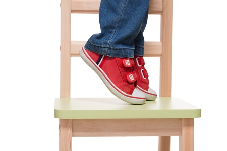 childs feet standing on the little chair on tiptoes on white background photo