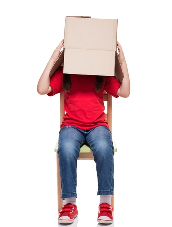 little girl sitting on chair wearing red t-shirt with box on head on white background photo