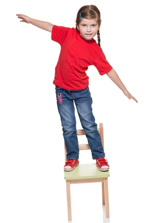 littlr gitl standing on a chair and balancing on white Stok Fotoğraf
