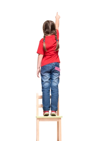 little girl wearing red t-shirt and pointing to  something up high on white background photo