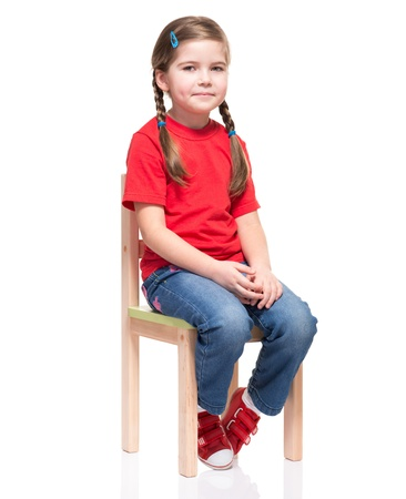 petite fille vêtue de rouge t-court et posant sur une chaise sur fond blanc