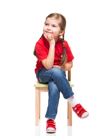 little girl wearing red t-short and posing on chair on white background