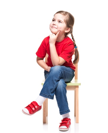girl looking up: little girl wearing red t-short and posing on chair on white background