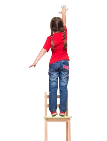 little girl wearing red t-shirt and reaching out something up high on white background photo
