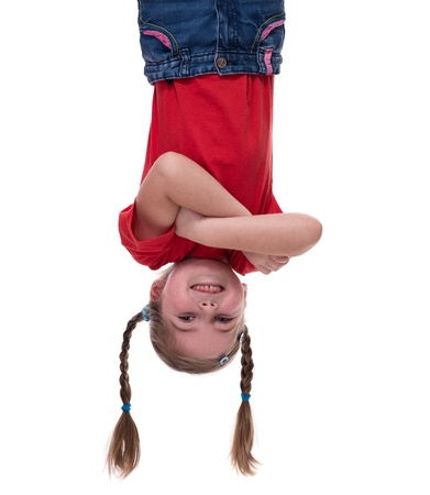 funny little girl hanging upside down on white photo