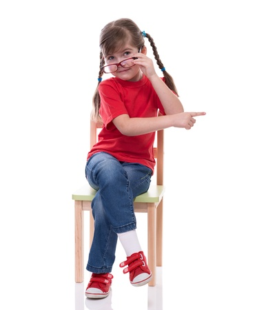 red tshirt: little girl wearing red t-shirt and glass pointing to somewhere or something isolated on white