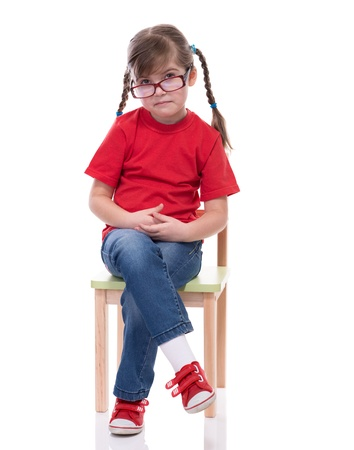 red tshirt: little girl wearing red t-shirt and glass posing on chair isolated on white