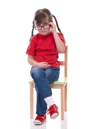 little girl wearing red t-shirt and glass posing on chair isolated on white photo