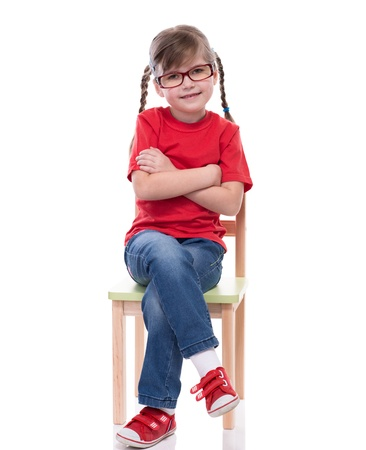 red tshirt: little girl wearing red t-shirt and posing on chair isolated on white