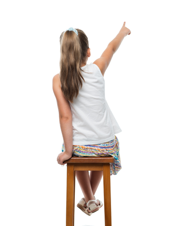 little girl sitting on chair and pointing aside