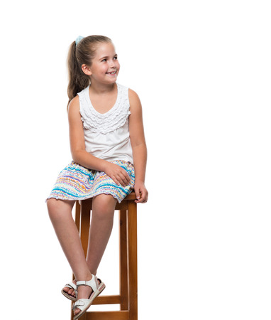 looking aside: little girl sitting on the chair and looking aside Stock Photo
