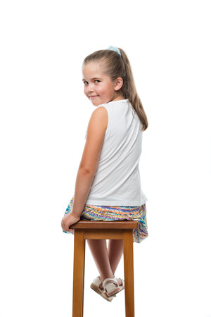 back view of little girl sitting on chair looking back to the camera