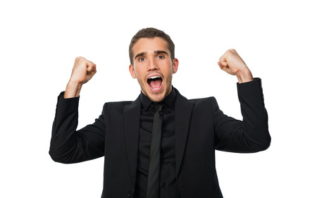 rejoices: young successful man put his hand up and rejoices victory