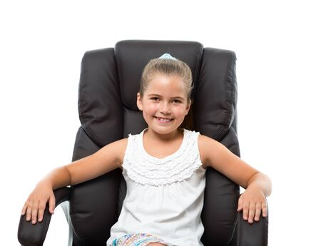 little girl sitting in big armchair and smiling photo