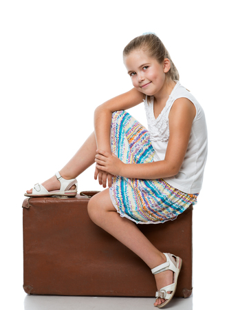 little girl siiting on the old brown suitcase photo