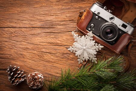 old items: composition of old fashioned photocamera ans xmas items on old wooden table