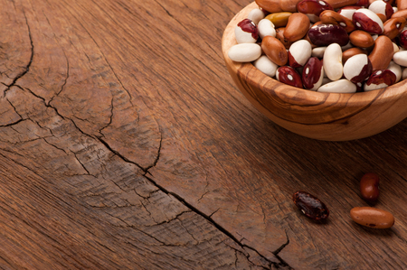 haricot: different sorts of haricot in wooden bowl on old table