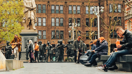 Street musician and people in Rembrandt Square in Amsterdam