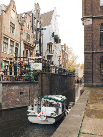 Boat and street cafe in Amsterdam, view of the canal