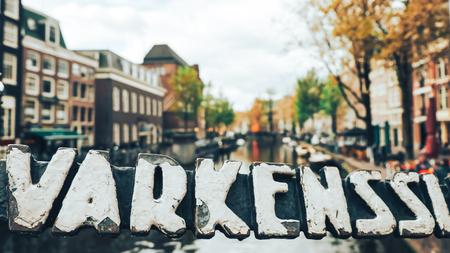 Symbol of Varkenssluis canal in Amsterdam, blurred background in summer