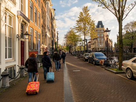 A group of tourists in Amsterdam with suitcases in the spring evening