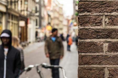 Peeking around the corner in Amsterdam Фото со стока
