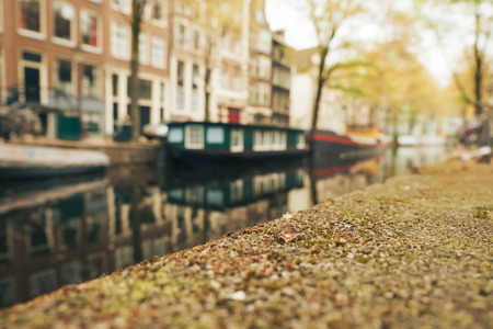 Canal and houseboat in Amsterdam. Blurred background. May 2017.