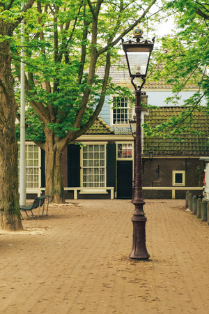 Old house in Amsterdam, a lantern and trees in the foreground. May 2017.