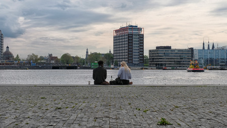 Amsterdam, The Netherlands - May 16, 2017. Young couple on the embankment of Amsterdam