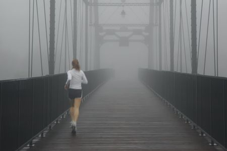 bad weather: Woman Jogging In Fog On Bridge Folsom California Stock Photo