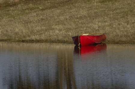the silence of the world: Red canoe on the shore of a pond and tree reflections  Stock Photo